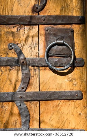 Wooden door adorned with wrought iron - stock photo
