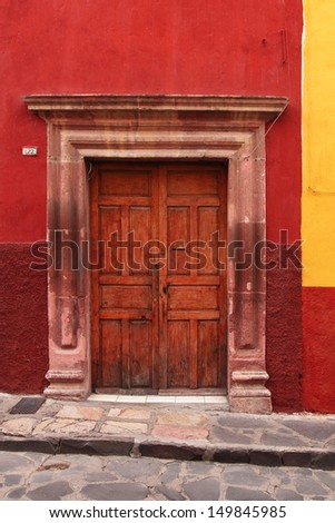 wooden door in red wall. typical mexican architecture - stock photo