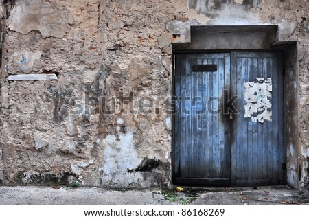 Wooden door in the dirty wall - stock photo