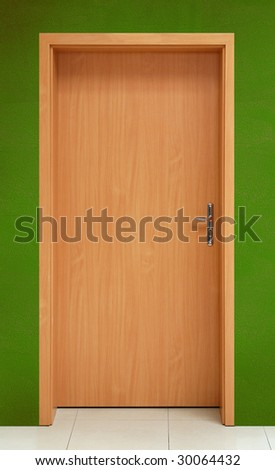 Wooden door on green wall background - stock photo