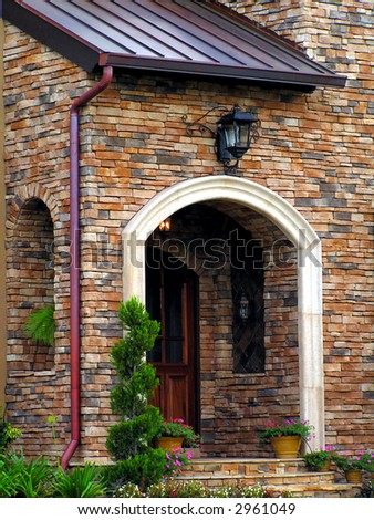 wooden door on stone home with archway - stock photo