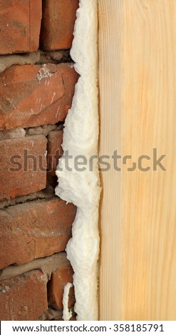 Wooden door or window install, closeup of polyurethane foam wood and bricks - stock photo