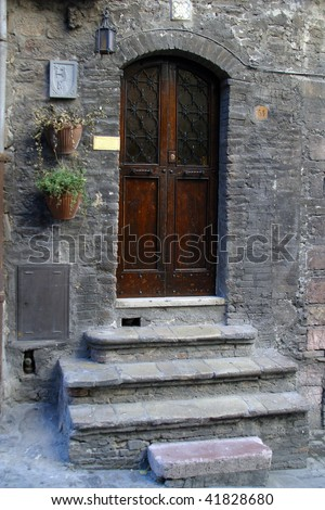 Wooden door with a stone door frame - stock photo
