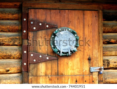 Wooden door with an unusual nautical porthole window and large hinges - stock photo