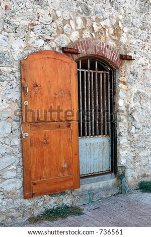 wooden door with gate on stone wall - stock photo