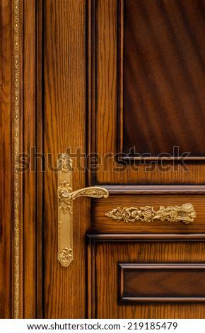wooden door with golden handle - stock photo