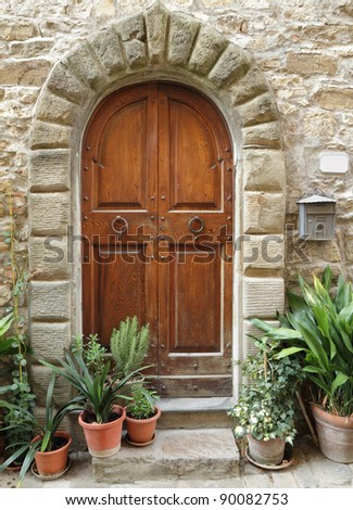 wooden door with stone arch to house in tuscan style,Tuscany,  Italy, Europe - stock photo