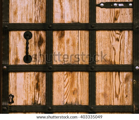 wooden door with wrought iron locked up - stock photo