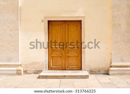Wooden doors in wall with doorsteps, front view - stock photo