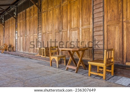 Wooden doors, table, chairs and floor of old Thai house - stock photo