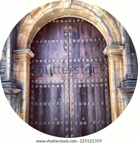 Wooden doors with bolts in a stone arched doorway. - stock photo