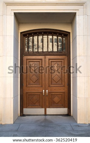 wooden double doors in the limestone facade of a building.
