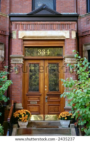 Wooden double doorway in Boston with trees and flowers - stock photo