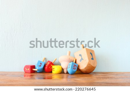 wooden dreidels for hanukkah (spinning top) over wooden background - stock photo
