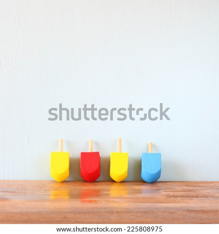 wooden dreidels for hanukkah (spinning top) over wooden background  - stock photo