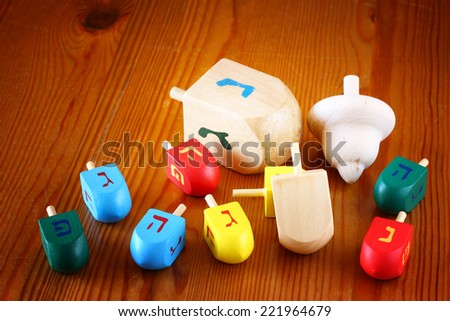 wooden dreidels (spinning top) for hanukkah jewish holiday over wooden table   - stock photo
