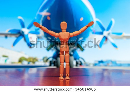 Wooden dummy, mannequin or man figurine of aviator stand against the backdrop of the aircraft before flight. Concept about airplanes, pilots and people. - stock photo