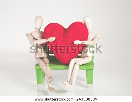 Wooden dummy. Sitting on the chair, green, embraces the heart,  by the background is gray. - stock photo