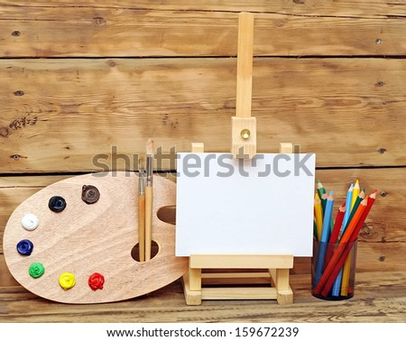 Wooden easel with clean paper and artistic equipment  - stock photo