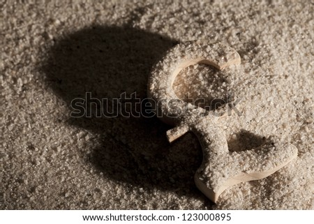 Wooden economy and currency unit in sand with shadow - stock photo