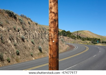 Wooden electric pole outdoor against winding highway - stock photo