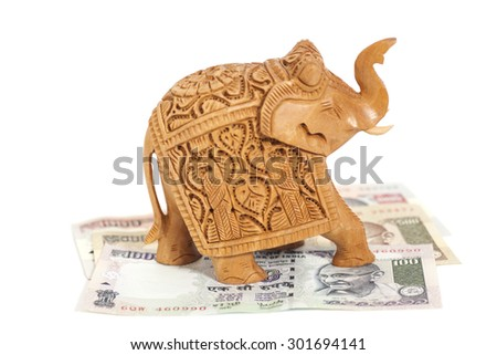 Wooden elephant sculpture on Indian  Rupee banknotes isolated on white - stock photo