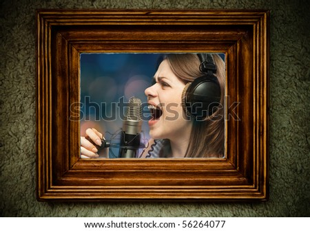 Wooden empty old frame on dirty  wall with portrait of singing woman inside
