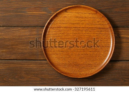 Wooden empty plate on a brown wooden background - stock photo