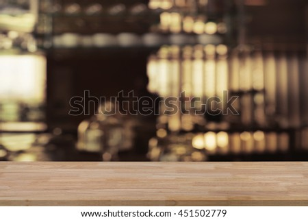 Wooden empty table top with defocus of pub or restuarant or cafeteria with bokeh light background, use for montage or product display, business concept - stock photo