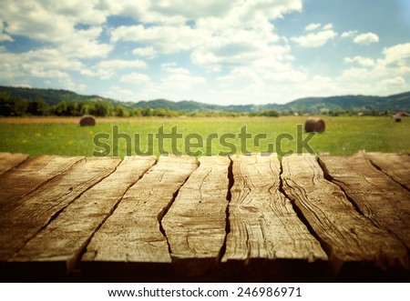 Wooden empty table. Wooden display with spring fields bokeh.  - stock photo