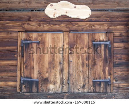 Wooden facade of a mountain hut  with closed window shutters and empty plate for content - stock photo
