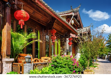 Wooden facade of traditional Chinese house decorated with red lanterns in the Old Town of Lijiang, Yunnan province, China. The Old Town of Lijiang is a popular tourist destination of Asia. - stock photo