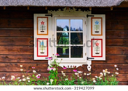Wooden facade with a retro (vintage) painted shutters. Window of the old house. Lithuania. - stock photo