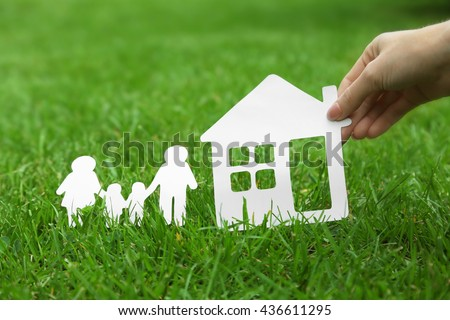 Wooden family shape on green grass background