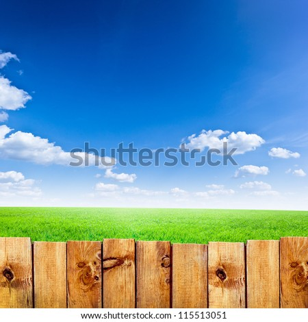 Wooden fence against green field and blue sky background