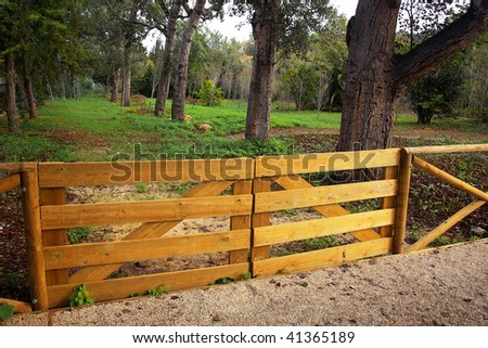 Wooden fence and doorway of a farming field with trees - stock photo