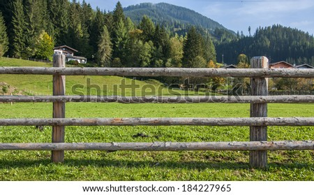 Wooden fence at ranch and green background - stock photo