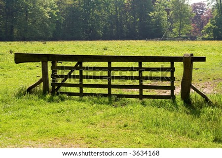Wooden fence at the border of a grass land. - stock photo