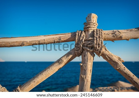 wooden fence element in the background of the sea. - stock photo
