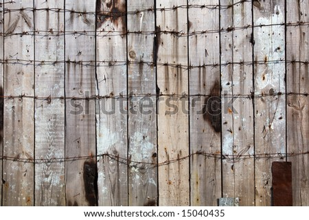 Wooden fence entangled by a barbed wire - stock photo