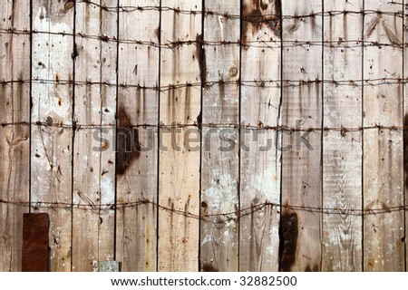 Wooden fence entangled by a barbed wire background - stock photo