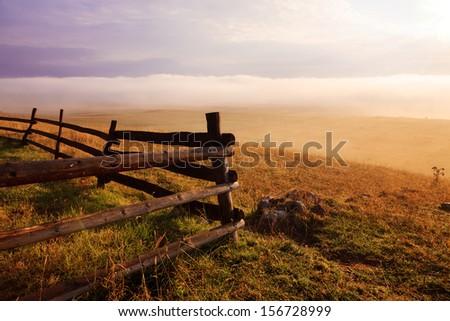 Wooden fence illuminated by morning light - stock photo