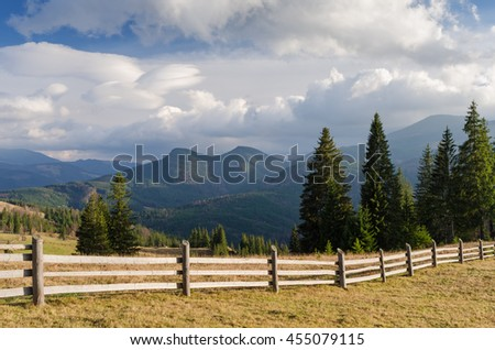 Wooden fence in a mountain village. Summer landscape with beautiful clouds and spruce forest on the slope. Sunny weather. Carpathians, Ukraine, Europe - stock photo