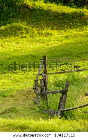 Wooden fence in country with grass - stock photo