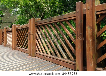 Wooden fence in garden with tree - stock photo