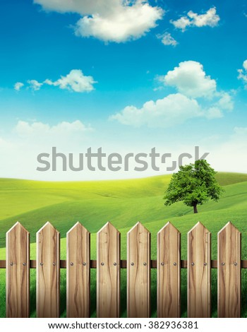 Wooden fence in green meadow - stock photo