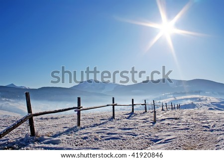 Wooden fence in snow covered mountains under shiny sun - stock photo