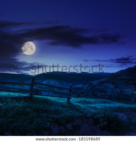 wooden fence in the grass on the hillside near the village at night in moon light - stock photo