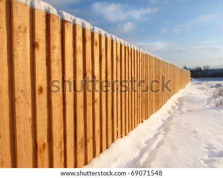 Wooden fence in the winter, amid the beautiful sky