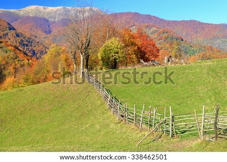 Wooden fence on a meadow and distant trees on a hill in autumn
